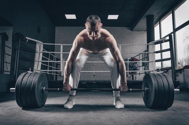Спортсмен стоит на коленях у перекладины и готовится сделать становую тягу.