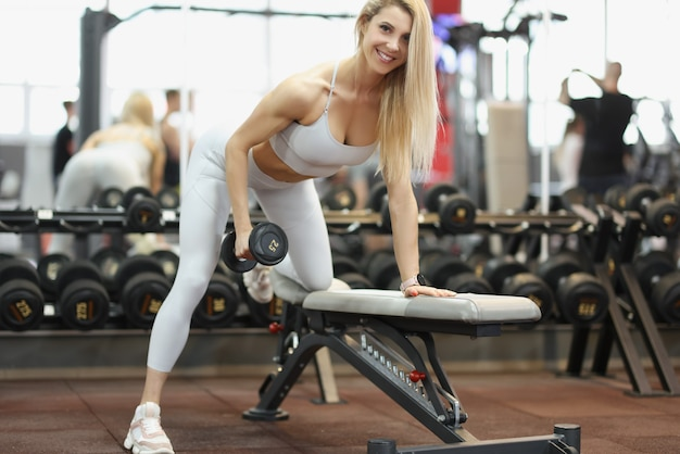 Athlete leans forward with dumbbells doing biceps exercises sport and beautiful body concept