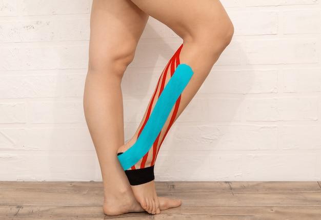 Ноги спортсмена и икры заклеены кинезиологической лентой. концепция здравоохранения и медицины