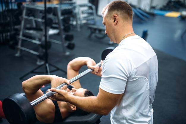 アスリートはベンチに横になり、インストラクターの管理下でバーベルを使って運動をします。モチベーションの方法、ジムのインテリア。