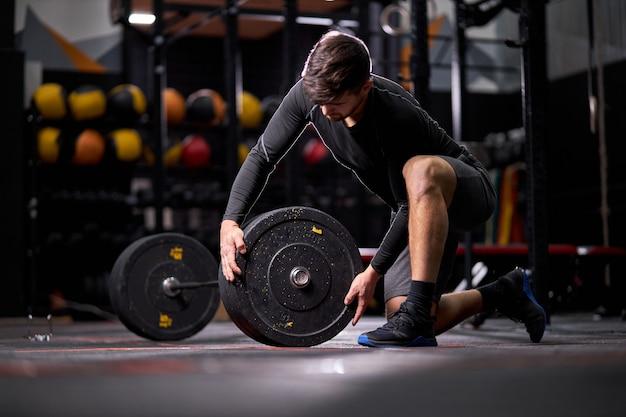 バーベルにウェイトプレートを追加しているアスリートの男性、ジムだけで重量挙げのトレーニングの準備をしている若い白人のフィットの男。ボディービルのコンセプト