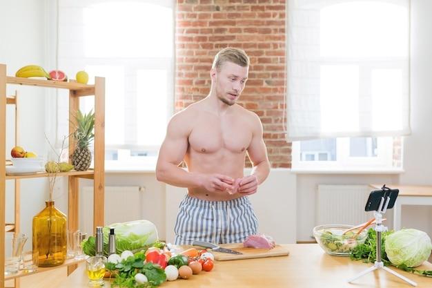アスリートの男性はキッチンで料理をし、夕食の調理に野菜やさまざまな肉を使用し、オンライン料理コースを視聴します