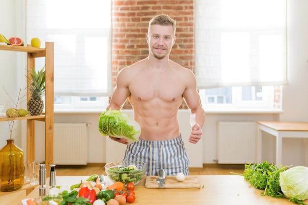 アスリートの男性はキッチンで料理をし、野菜やさまざまな肉を使って夕食を作ります