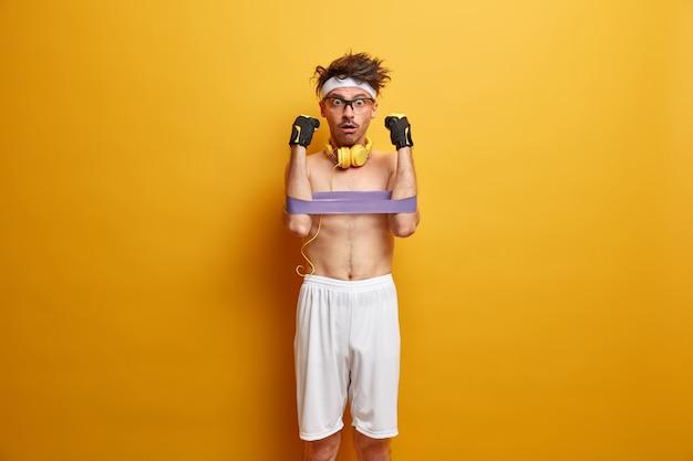 アスリートの男性は、フィットネスガムで手の筋肉を発達させ、ショックを受けた表情で凝視し、白いショートパンツ、ヘッドバンドを着用し、黄色の壁に隔離されたステレオヘッドフォンを使用します。強く健康を保つ