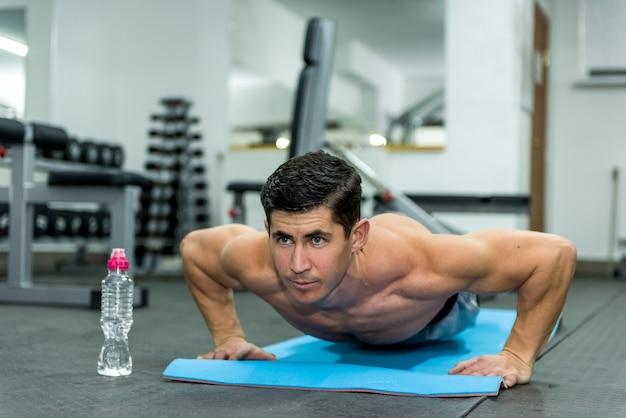 Спортсмен мужчина делает отжимания в спортивном тренажерном зале