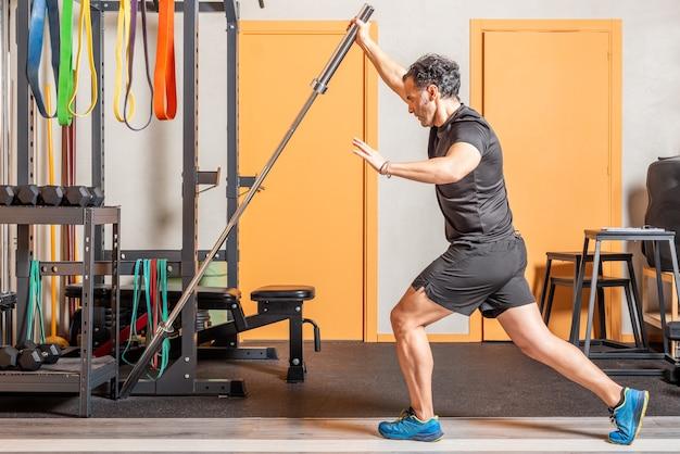 ジムでバーと立っている運動をしている運動選手の男。ジムでの機器を使った運動の概念。