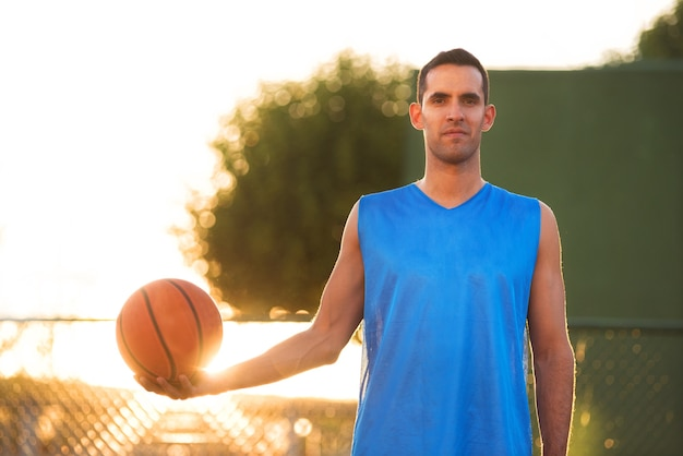 Athlete man holding basketball ball standing on playground at sunset