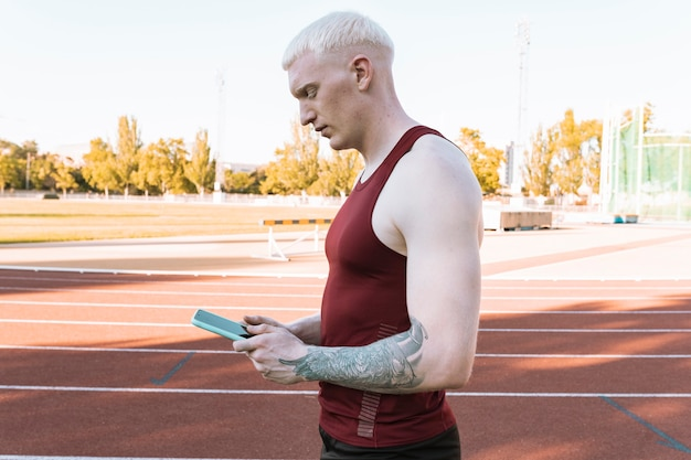 육상 트랙에서 운동선수 남자, 그의 스마트폰을 보고