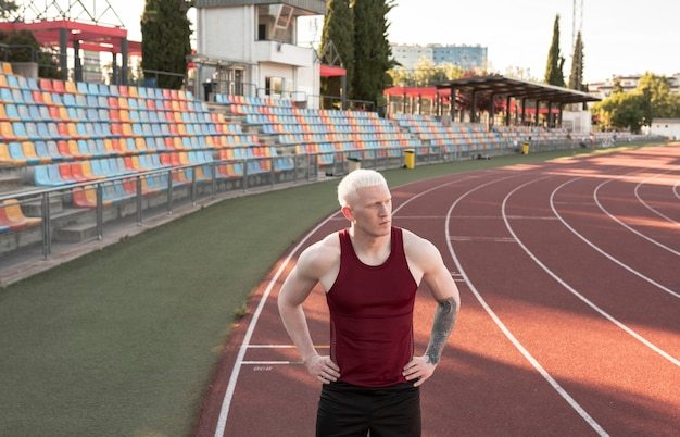 Athlete man in relaxation posture, on a running track