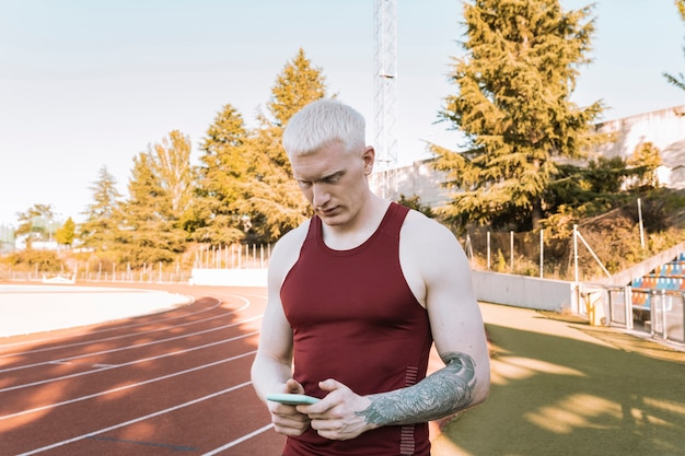 Athlete man on running track, looking at his smarpthone