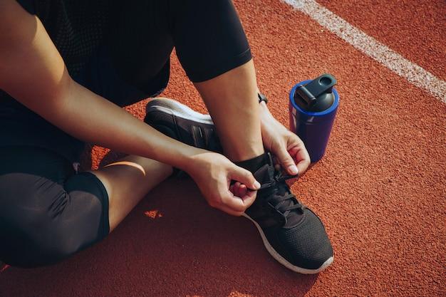 Athlete man sitting on a shoelace  at the stadium.start