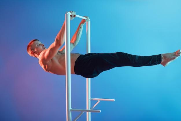 アスリートの男性が鉄棒でトレーニング、裸足でトップレスのポーズをとって、黒いズボンを履いて、男がクロスバーでワークアウト、ハンサムなスポーツマンがスポーツをしています。