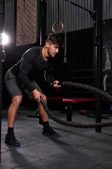 アスリートの男性がロープでトレーニングし、クロスフィットのバトルロープが一人で運動し、屋内で、モダンなジムで激しいトレーニングを行います。スポーツの動機付けの概念。スペースをコピーします。