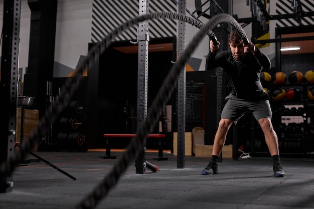 Athlete man training with rope, cross fit battle ropes exercise alone, intense workout indoors, in modern gym. sport motivation concept. copy space.