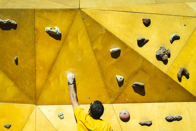 Athlete man trying to reach the top of a climbing wall with the strength of his hands and legs.