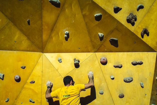彼の手と足の強さでクライミングウォールの頂点に到達しようとしている運動選手男