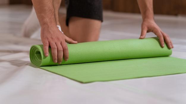 운동 선수 남자는 롤 매트를 풀고 스포츠 장소를 준비합니다. 신체 훈련을하는 결정된 사람