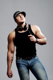 ヘッドフォンを身に着けている大きな筋肉を持つアスリート男