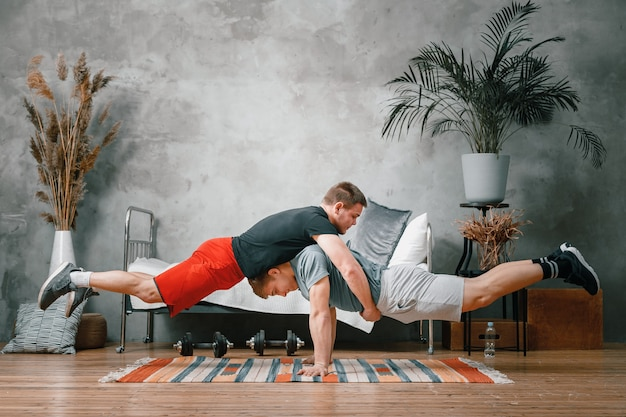The athlete men makes a plank on top of each other in the bedroom, in the background a bed, a vase, a carpet. gymnasts training, acrobats' home tricks