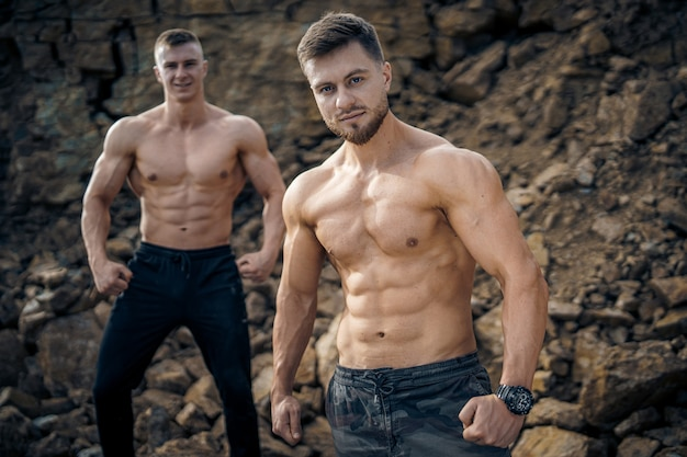 Athlete men on a rocky background. perfect bodies. quarry or mountain background.