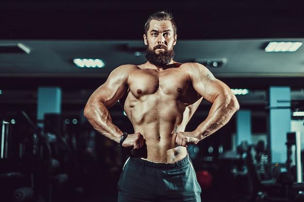 Athlete muscular bodybuilder man posing in gym.