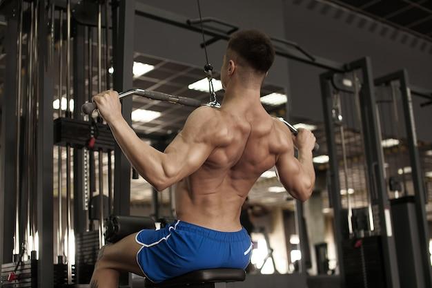 Спортсмен мускулистый культурист тренируется на тренажере в тренажерном зале