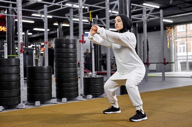 健康と健康のために運動しているフィットネスセンターで屋内でしゃがむスポーツヒジャーブの運動選手のイスラム教徒の女性。スポーツ、フィットネス、コンセプト