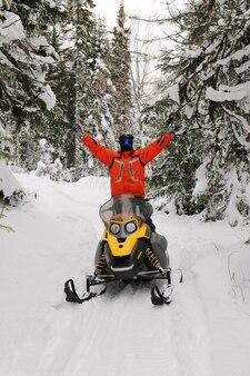 南ウラル山脈の冬の森を移動するスノーモービルの選手。