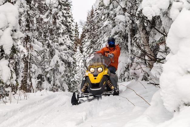 Спортсмен на снегоходе передвигается по зимнему лесу в горах южного урала.