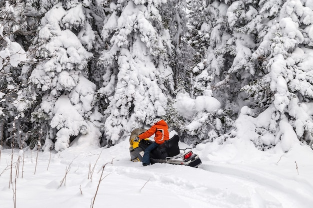 冬の森を移動するスノーモービルのアスリート