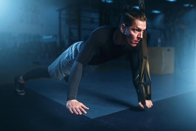 Спортсмен на тренировке, упражнения отжимания со скакалкой в тренажерном зале.