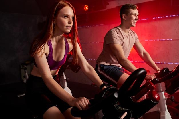 ジム、サイクリングマシンの自転車、トラックスーツを着て運動や運動をしているアスリートの人々。トレーニング、健康、フィットネスの健康