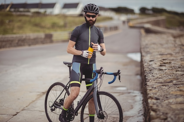 Athlete refreshing from bottle while riding a bicycle
