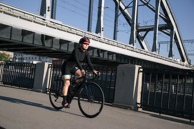 Спортсмен едет на велосипеде под железнодорожным мостом