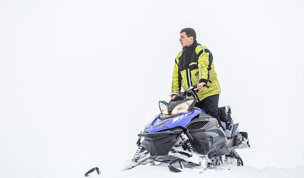 Спортсмен катается на снегоходе в горах.