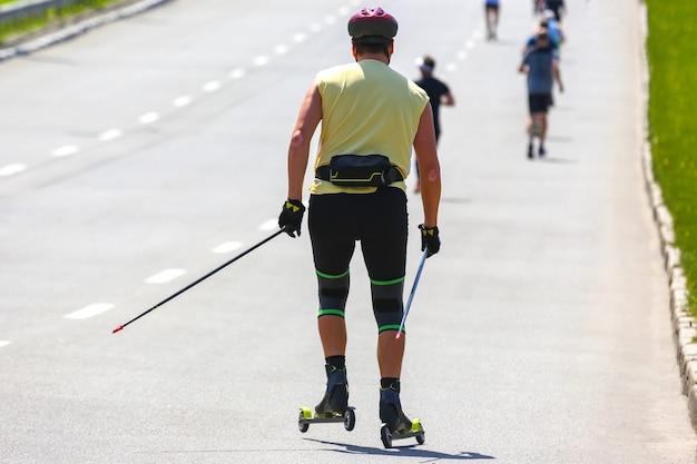 アスリートが道路のアスファルトでローラー スキーに乗る