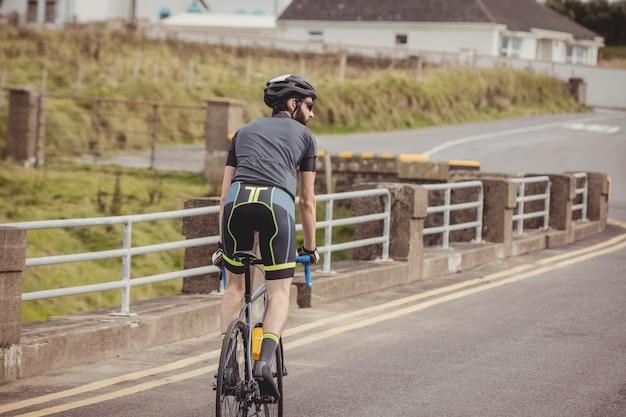 Спортсмен, едущий на велосипеде по дороге
