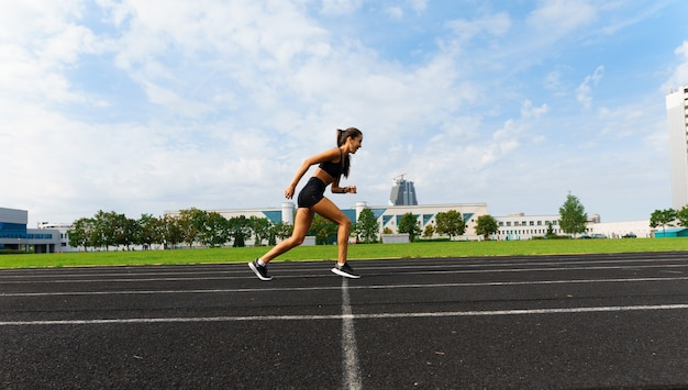 Athlete runner running on athletic track training her cardio. woman jogging for competition race at summer outdoor stadium.