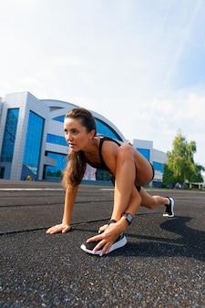 彼女の心肺機能を訓練する運動トラックで走っているアスリートランナー。夏の屋外競技場での競技レースのためにジョギングしている女性。