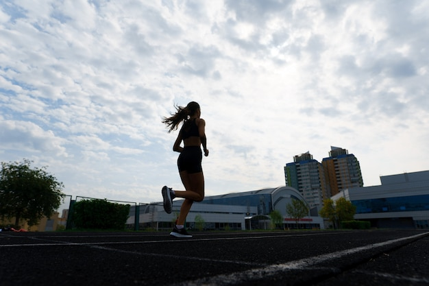 Бегун спортсмена работает на спортивной трассе тренировки ее кардио.