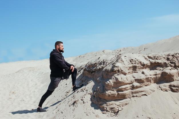 自然の中でトレーニングする前に足を伸ばすアスリートランナー