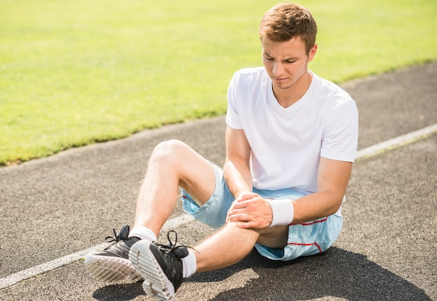 Athlete runner touching foot in pain due to sprained ankle.