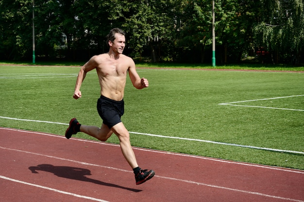 Athlete runner trains at the stadium