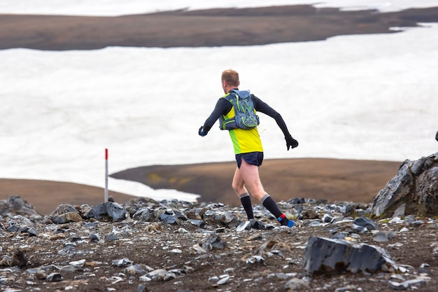 선수들이 landmannalaugar의 눈 덮인 지형에서 산악 마라톤을 실행합니다.