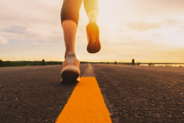 마라톤 및 피트니스 일몰 훈련에서 도로 트레일에서 실행하는 선수. 야외에서 운동하는 여자의 동작 흐림 효과