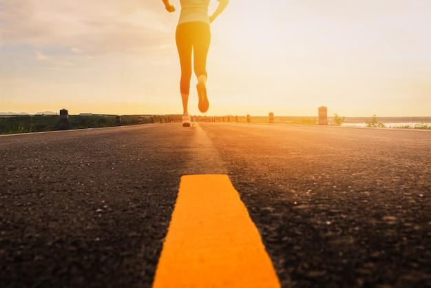 マラソンとフィットネスのためのサンセットトレーニングでロードトレイルを走っているアスリート。屋外で運動する女性のモーションブラー