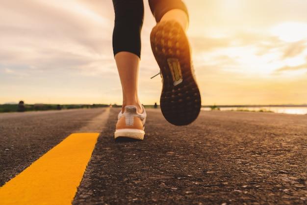 日没のトレーニングで道路の道を走っている選手。屋外で運動する女性のモーションブラー