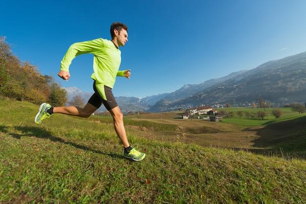 선수는 이탈리아 알프스 계곡의 초원에서 내리막 길을 달리고 있습니다.