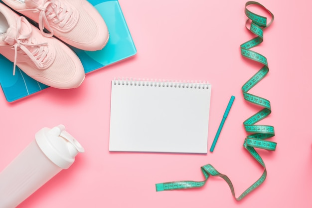 Athlete's set. sports equipment - running shoes, scales, measuring tape and protein plastic shaker on pastel pink background.