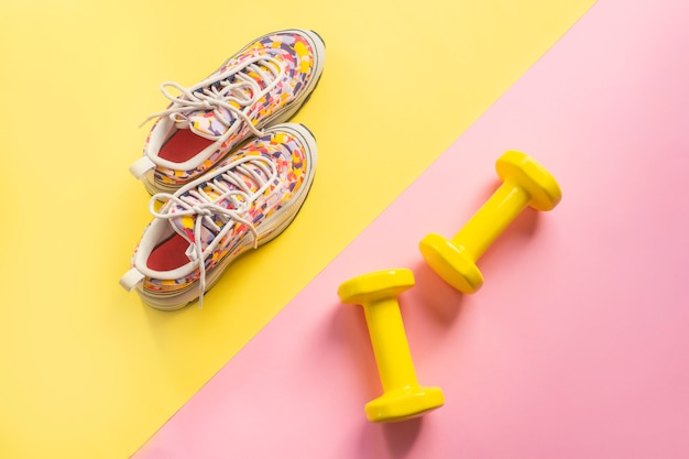 Athlete's set with female running sneakers and dumbbells yellow-pink background.